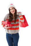 Smiling brunette holding gifts and showing shopping bag Royalty Free Stock Images