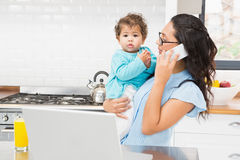 Smiling brunette holding her baby and using laptop on phone call Stock Image