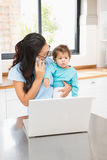 Smiling brunette holding her baby and using laptop on phone call Royalty Free Stock Image