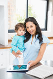 Smiling brunette holding her baby and using tablet Royalty Free Stock Photography