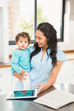 Smiling brunette holding her baby and using tablet Stock Photo