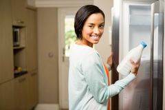 Smiling brunette holding milk bottle with open refrigerator Stock Image
