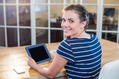 Smiling brunette holding tablet Stock Image
