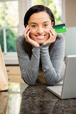 Smiling brunette in kitchen holding credit card Stock Photography