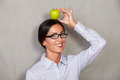 Smiling brunette lady holding apple on head Royalty Free Stock Photos