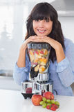 Smiling brunette leaning on her juicer full of fruit Royalty Free Stock Photography