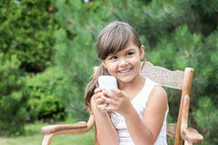 Smiling brunette little girl with smart phone outdoors royalty free stock photography