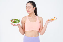 Smiling brunette looking at salad while holding pizza Stock Photos
