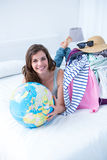 Smiling brunette lying on bed holding her globe Royalty Free Stock Image
