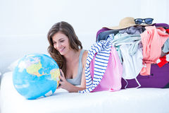 Smiling brunette lying on bed looking her globe Royalty Free Stock Photos