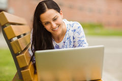 Smiling brunette lying on bench using laptop Stock Images