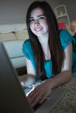 Smiling brunette lying on floor using laptop in the dark looking Stock Photos
