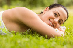 Smiling brunette lying on grass Stock Photo