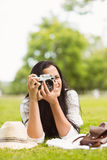 Smiling brunette lying on grass taking picture Royalty Free Stock Photography
