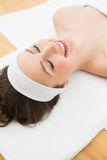 Smiling brunette lying on massage table in beauty salon Stock Photography