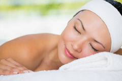 Smiling brunette lying on massage table with eyes closed Royalty Free Stock Images