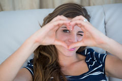 Smiling brunette making heart with her hands Royalty Free Stock Photo