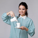 Smiling brunette with a milk pot and a cup stock photography