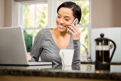 Smiling brunette on phone call while looking at laptop Stock Images