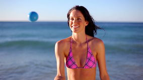 Smiling brunette playing with a ball Royalty Free Stock Image