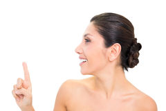 Smiling brunette pointing up with one hand with head turned Royalty Free Stock Image