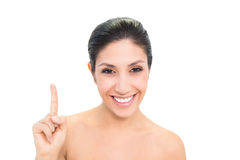 Smiling brunette pointing up with one hand Stock Photography