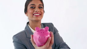 Smiling brunette putting notes in a piggy bank Royalty Free Stock Photo