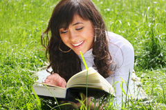 Smiling brunette reading book on grass Royalty Free Stock Images