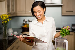 Smiling brunette reading book and preparing smoothie Stock Image