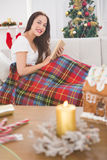 Smiling brunette reading on the couch with cover Royalty Free Stock Photos