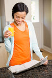 Smiling brunette reading newspaper and holding glass with orange juice Royalty Free Stock Photography
