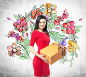 A smiling brunette in a red dress holds an orange gift box. The sketch of colourful flowers is drawn on the concrete wall Stock Image
