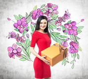 A smiling brunette in a red dress holds an orange gift box. The sketch of purple flowers is drawn on the concrete wall Stock Images