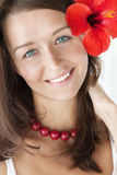 Smiling brunette with red flower. Close up portrait of beautiful brunette with red flower Stock Photography