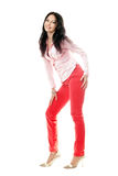 Smiling brunette in red jeans Royalty Free Stock Image