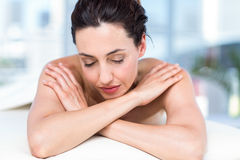 Smiling brunette relaxing on massage table Royalty Free Stock Image