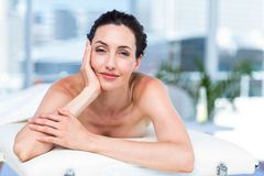 Smiling brunette relaxing on massage table Stock Photos
