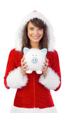 Smiling brunette in santa claus holding a piggy bank Royalty Free Stock Images