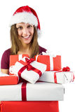 Smiling brunette in santa hat holding pile of gifts Royalty Free Stock Image