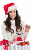 Smiling brunette in santa hat packing gifts Royalty Free Stock Photography