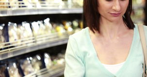 Smiling brunette shopping with grocery list. Portrait of smiling brunette shopping with grocery list in grocery store stock video