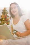 Smiling brunette shopping online with laptop at christmas Royalty Free Stock Images