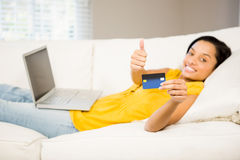 Smiling brunette showing credit card Royalty Free Stock Images