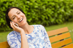 Smiling brunette sitting on bench phoning Royalty Free Stock Photos