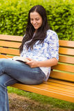 Smiling brunette sitting on bench reading Royalty Free Stock Images