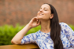 Smiling brunette sitting on bench relaxing Royalty Free Stock Image