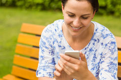 Smiling brunette sitting on bench texting Stock Photo
