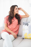 Smiling brunette sitting on her couch looking away Stock Photo