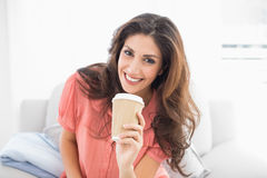 Smiling brunette sitting on her sofa holding disposable cup Royalty Free Stock Photo