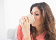 Smiling brunette sitting on her sofa sipping from disposable cup Stock Image